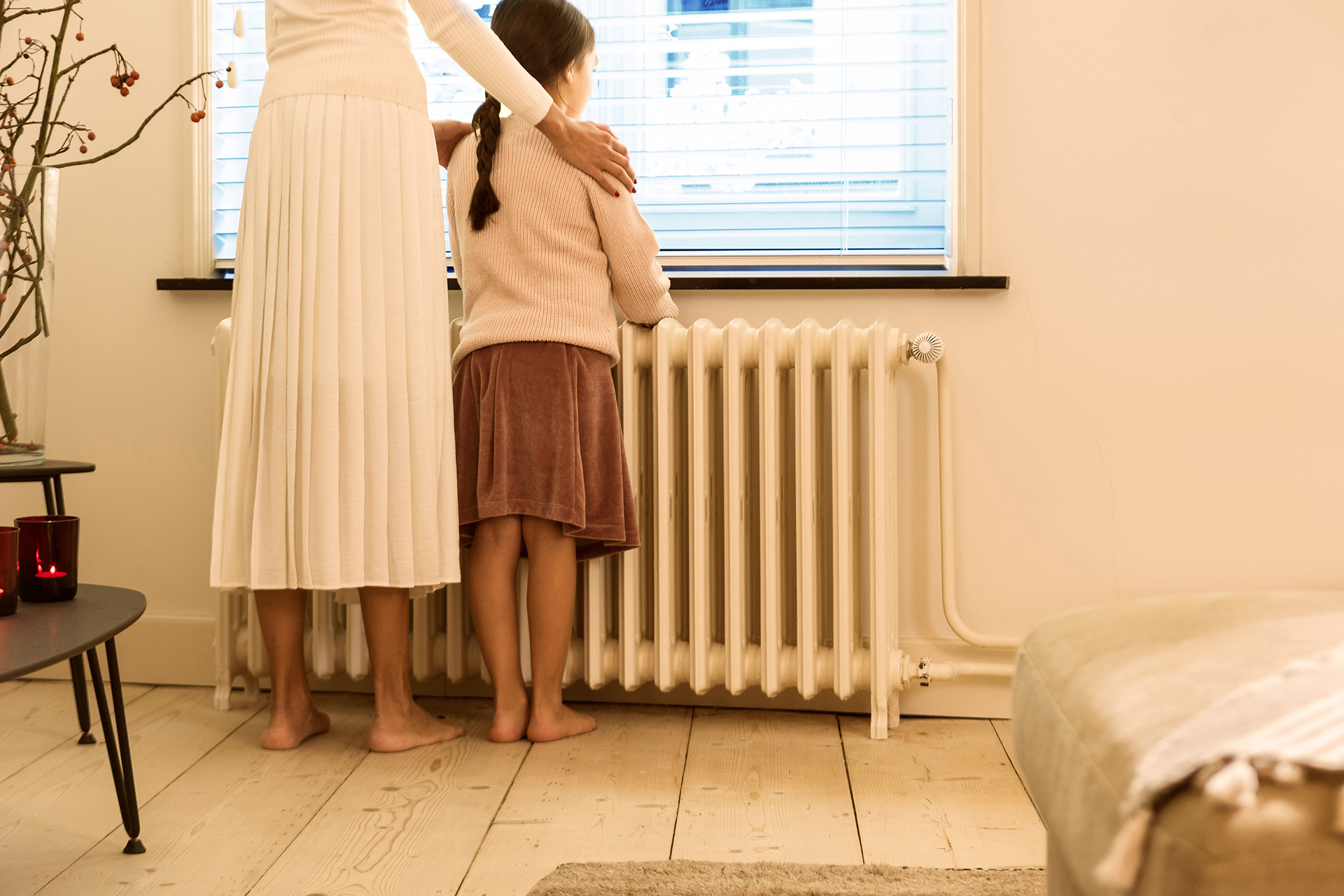 Young girl and mother looking out of window touching old radiator
